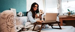 Woman smiling with dog looking at laptop