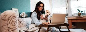 Woman smiling with dog looking at laptop cropped 2