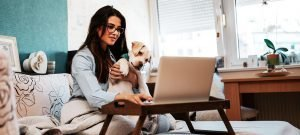 Woman smiling with dog looking at laptop cropped 3
